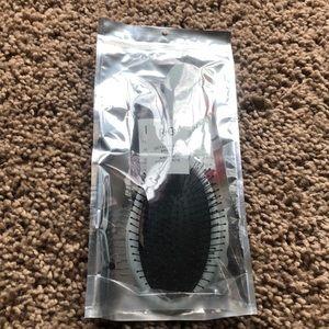 In original packaging. R+Co detangling brush